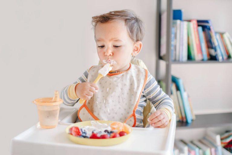 bambino di 18 mesi si gode il suo spuntino seguendo un'alimentazione corretta
