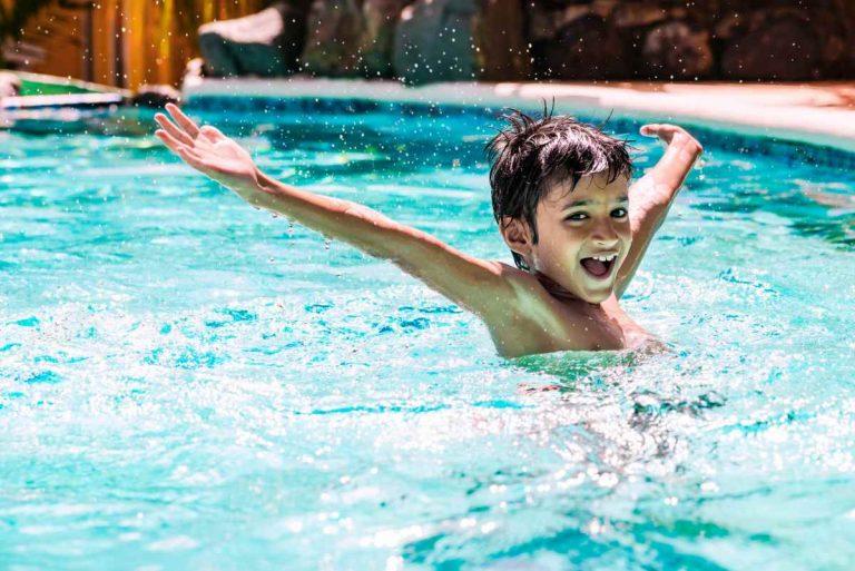 bambino gioca in piscina e con i suoi giochi per l'acqua